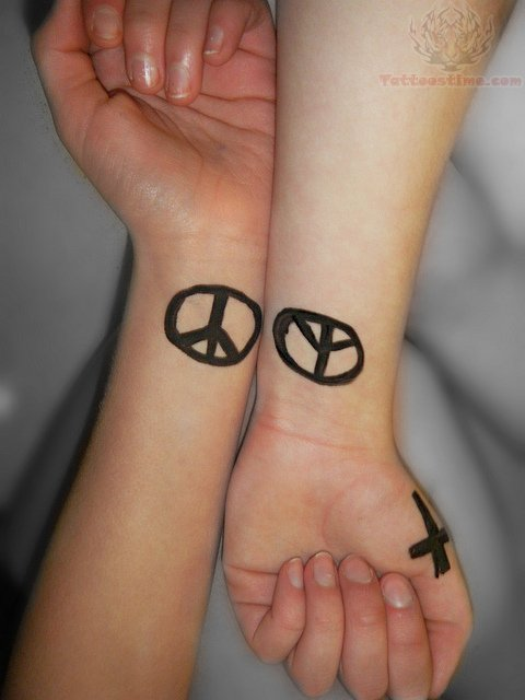 peace symbol tattoos on wrists