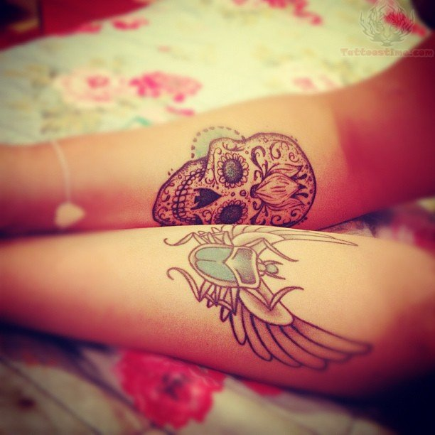 Winged Bug And Sugar Skull Tattoos On Arm