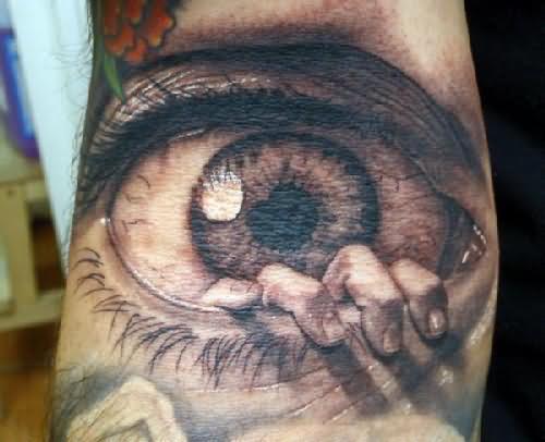 Big eye and hand tattoo