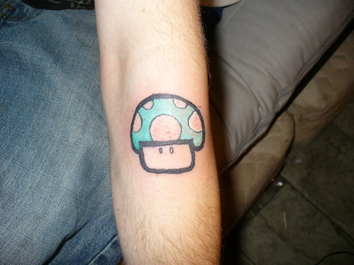 Blue ink mario mushroom tattoo on arm for Mario mushroom tattoo