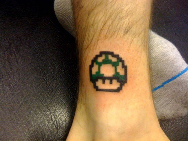Green ink mario mushroom tattoo on ankle for Mario mushroom tattoo
