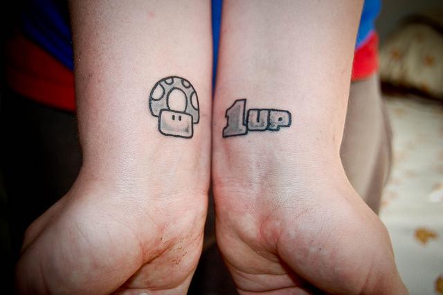 Grey Ink Mario 1 Up Mushroom Tattoos On Wrist
