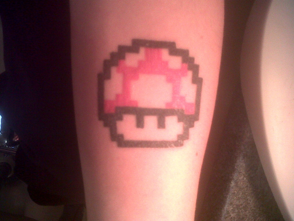 Red ink mario mushroom tattoo on arm for Mario mushroom tattoo