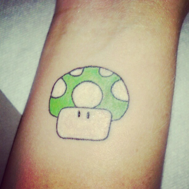 Green ink mario mushroom tattoo on arm for Mario mushroom tattoo