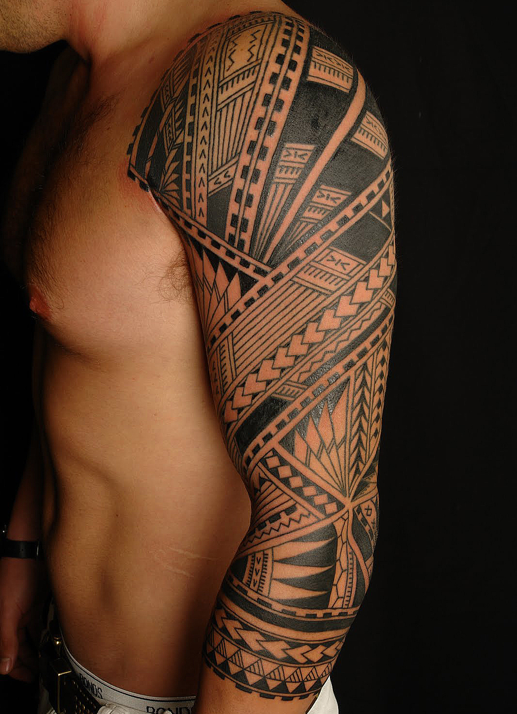 Amazing black ink tribal tattoo on man left sleeve for Tribal half sleeve tattoos