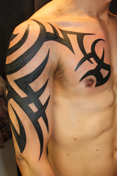 black ink tribal tattoo on right half sleeve and chest. Black Bedroom Furniture Sets. Home Design Ideas