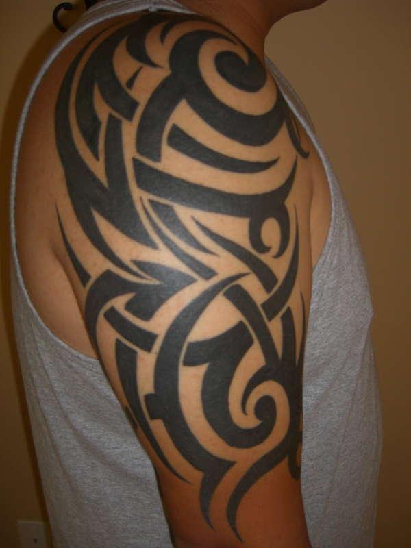 black ink tribal tattoo on right half sleeve