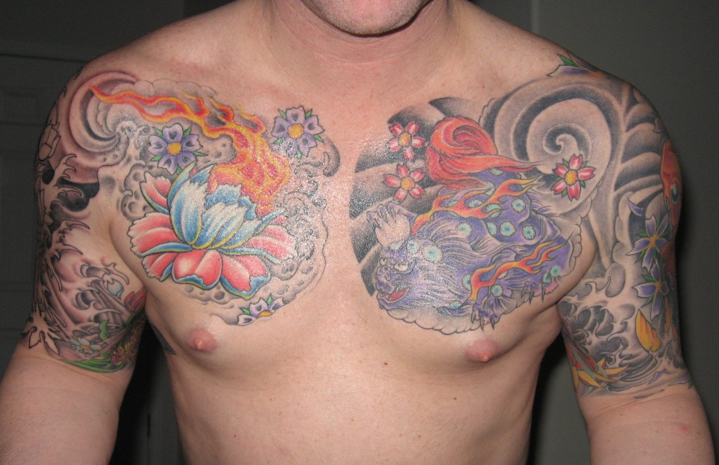 Colored Lotus Flower Tattoo On Man Chest