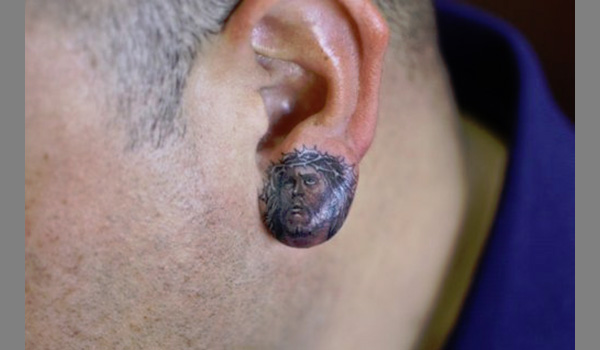 Grey Ink Jesus Head Ear Lobe Tattoo