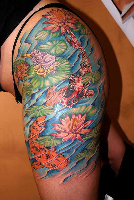Colored koi fish and colored flowers tattoos on girl left for Colorful thigh tattoos