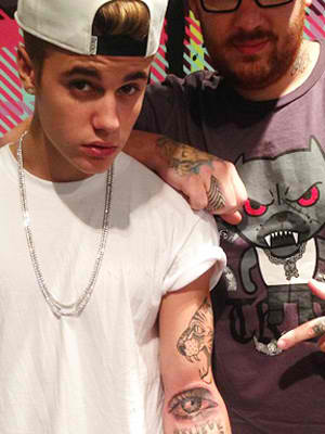 Justin beiber lion head and eye tattoo on left sleeve for Justin bieber eye tattoo