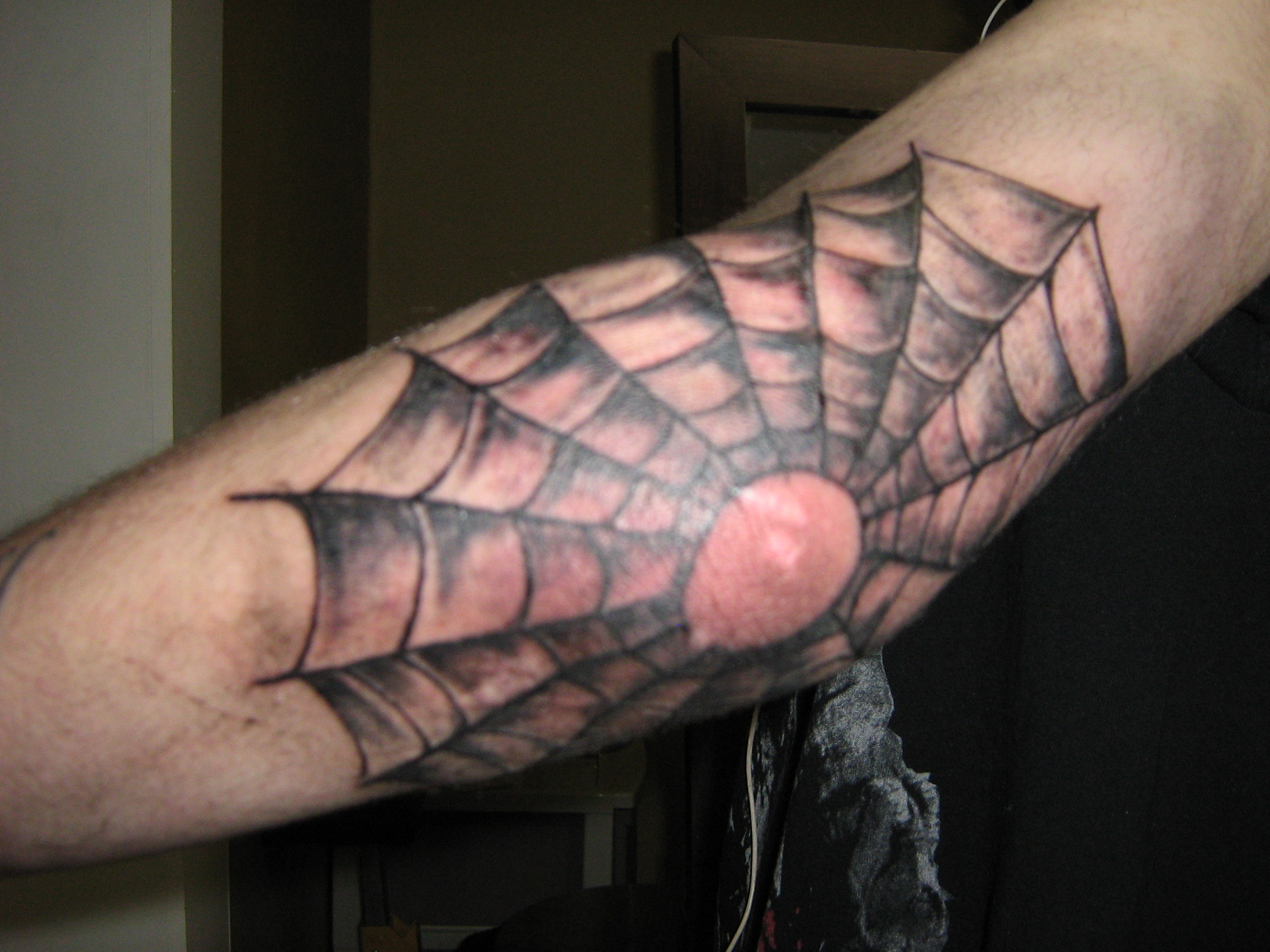 Tattoo of spider web on elbow