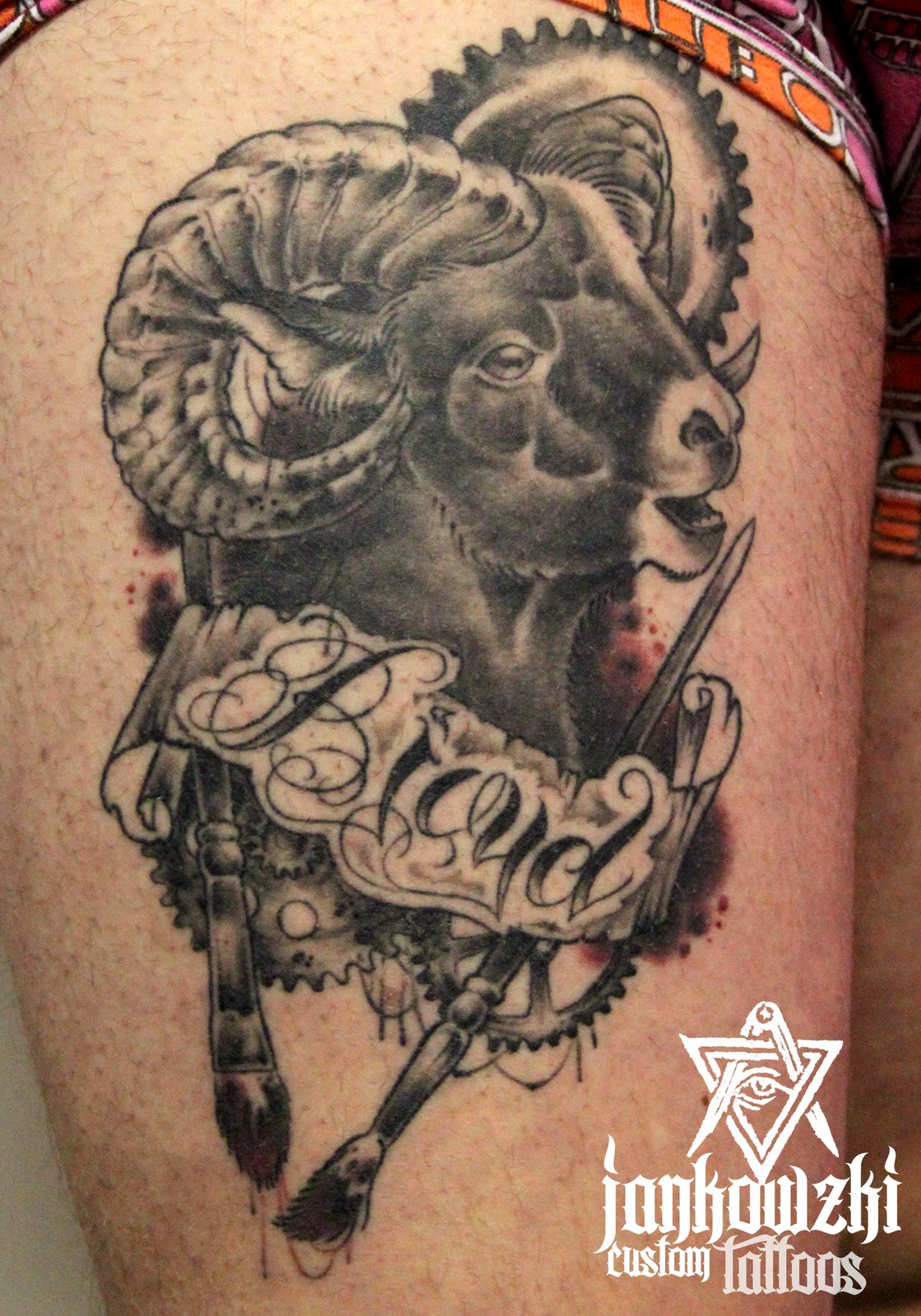 Grey Ink Banner And Aries Head Tattoo