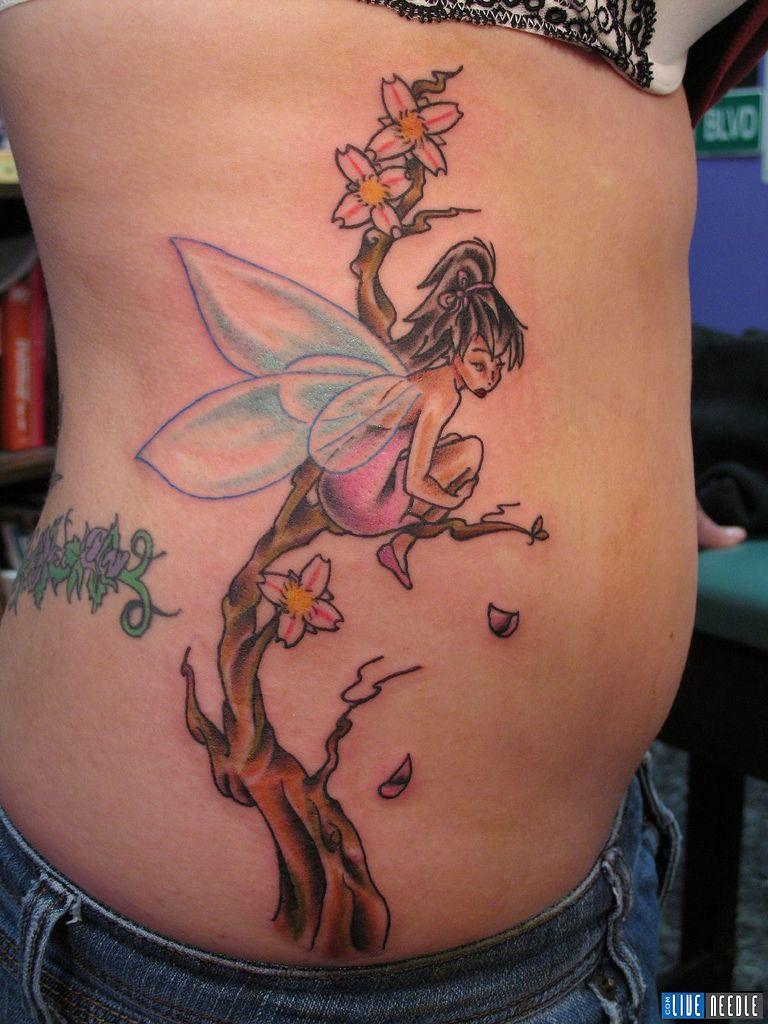colored ink fairy sitting on tree tattoo on side rib. Black Bedroom Furniture Sets. Home Design Ideas