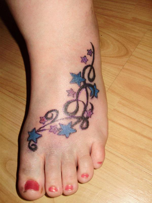Colored stars and tribal left foot women tattoo for Women foot tattoos