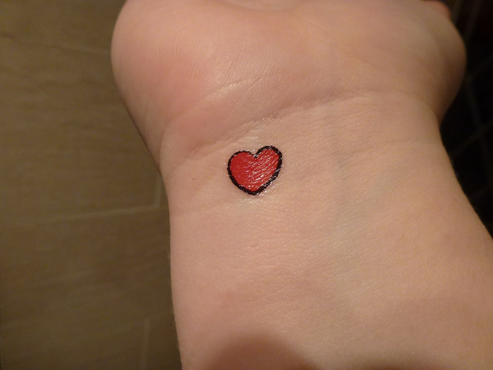 Tiny red heart tattoo on wrist for Small heart tattoos on wrist