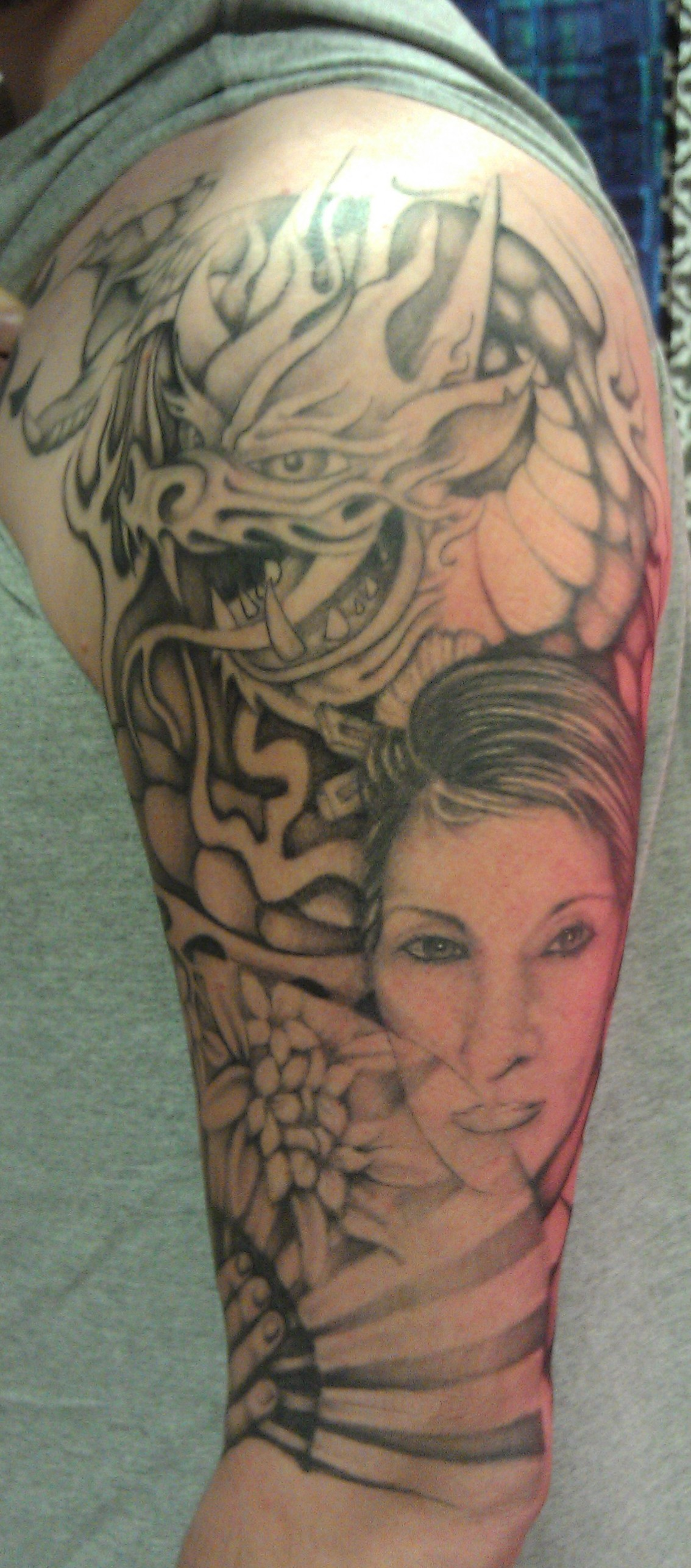Grey Ink Geisha Tattoo On Man Left Sleeve