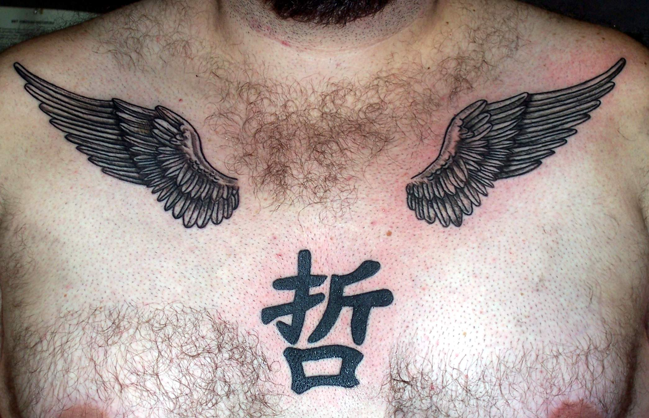 Kanji Symbol And Wings Tattoos On Man Chest