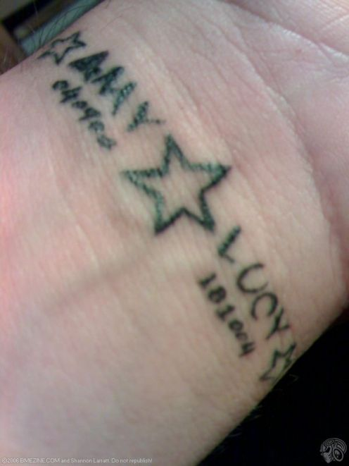 Black Ink Star And Baby Names Tattoo On Wrist