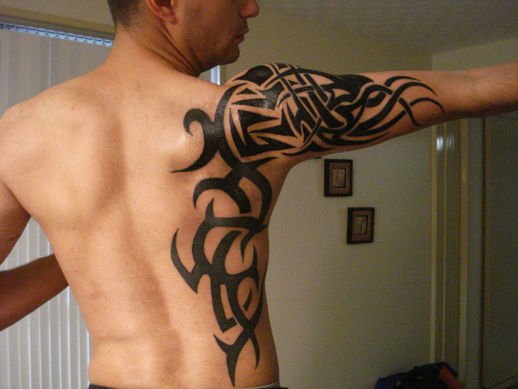 9d515114bf382 Black Ink Tribal Tattoo On Side And Right Arm