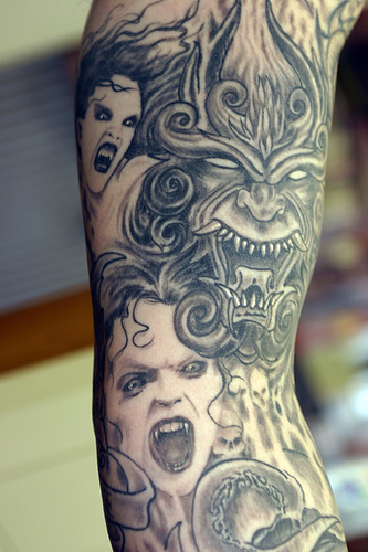 Grey Ink Evil Tattoo On Right Arm