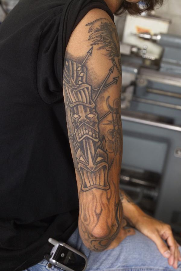 Grey ink tikki tattoo on right arm for Tattoos on right arm