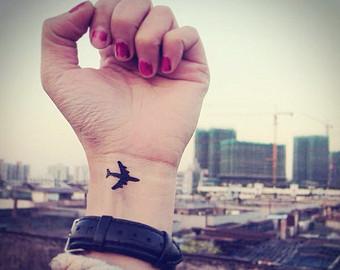 Black Ink Small Airplane Tattoo On Left Wrist