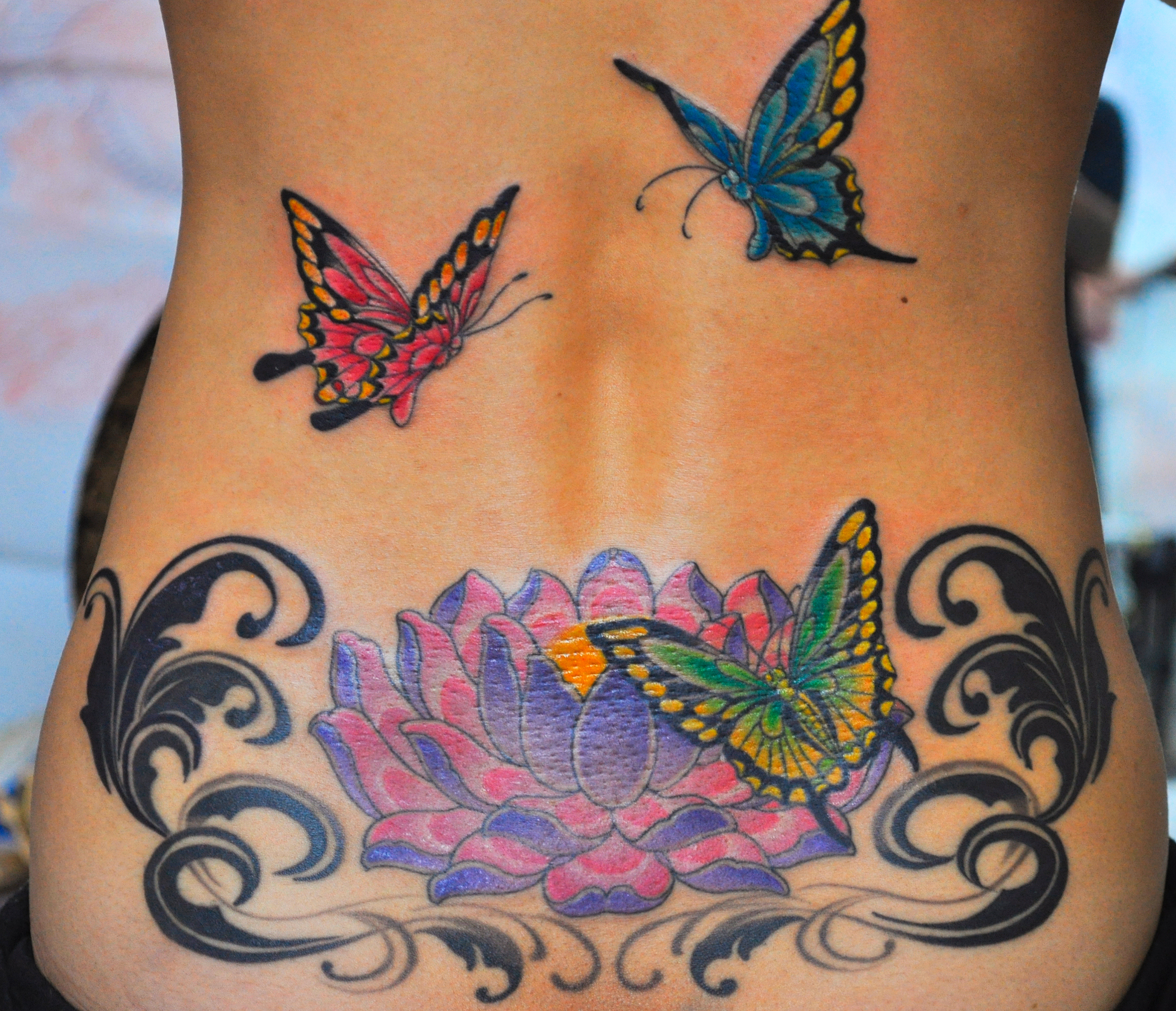 Colored Butterflies And Lotus Tattoo On Lowerback