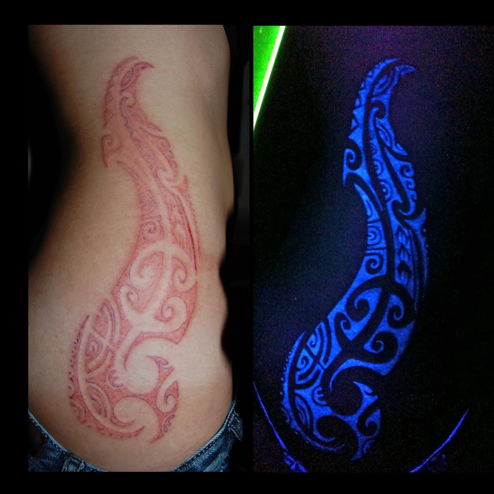 44d1763fb6238 Tribal Red Ink And Black Light Tattoo On Side Rib