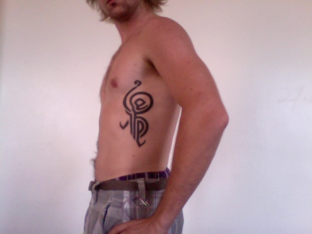 Black Tribal Hakuna Matata Tattoo On Man Left Side Rib