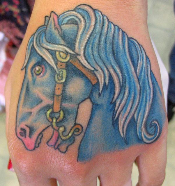 Blue ink horse tattoo on left hand for Blue horseshoe tattoo