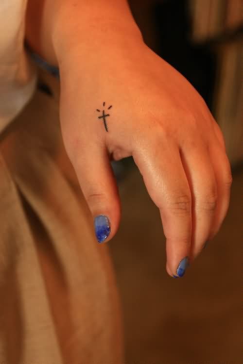 showing small cute cross tattoo
