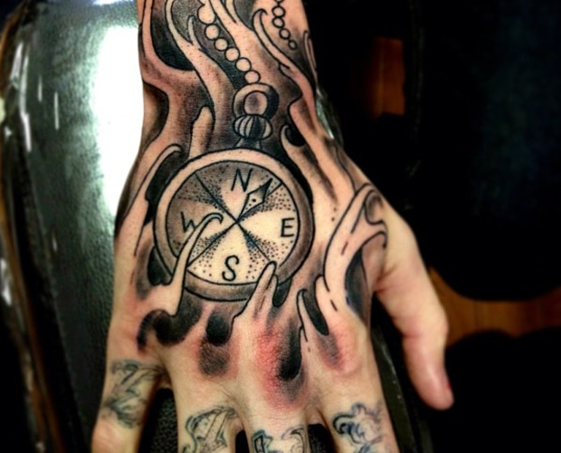 Compass with chain & ripped skin tattoo on back hand