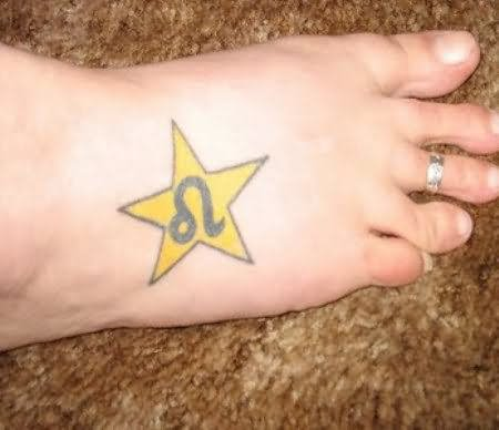 Yellow Star With Leo Sign Tattoo On Foot