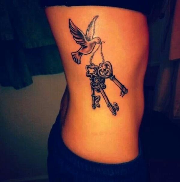 Bird Flying With Keys Tattoo On Rib Side