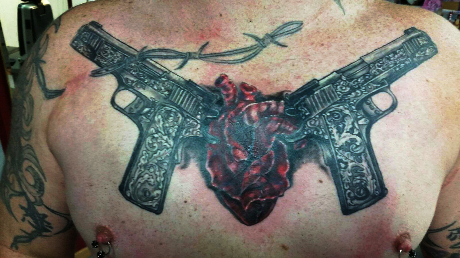 Black And Grey Guns With Red Heart Tattoo On Chest
