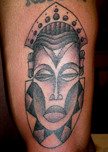 African Mask Tattoo On Left Bicep