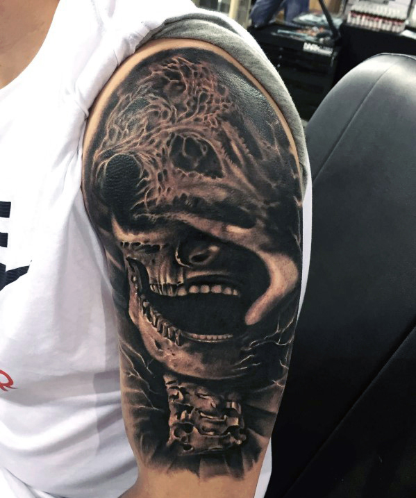Black And Grey Skull Tattoo On Man Left Arm