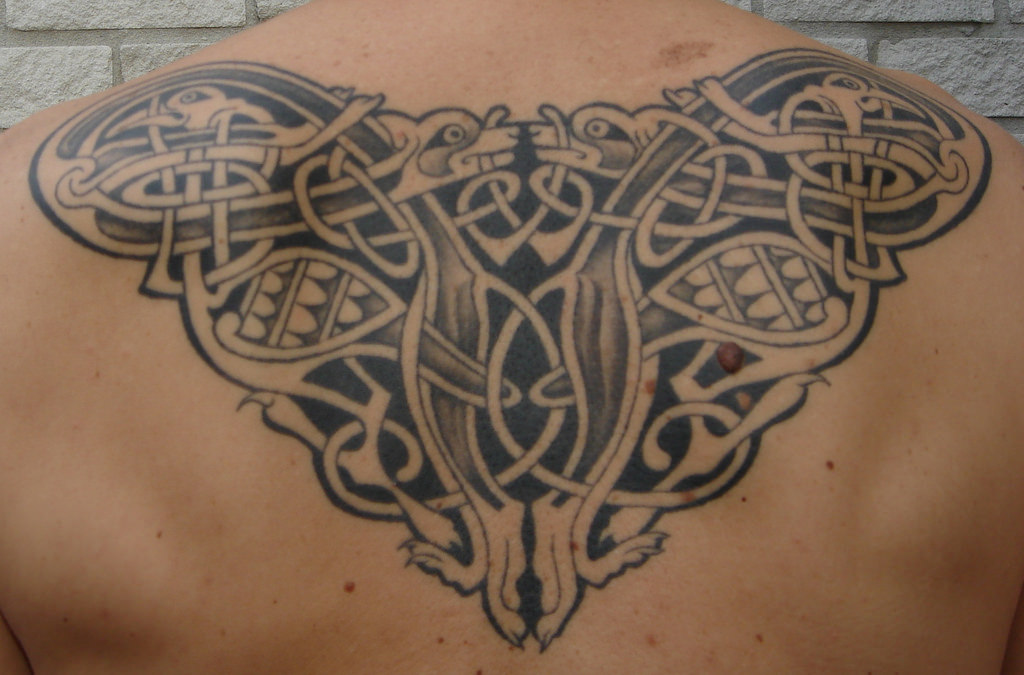 Nice Black And Grey Celtic Symbol Tattoo On Upper Back