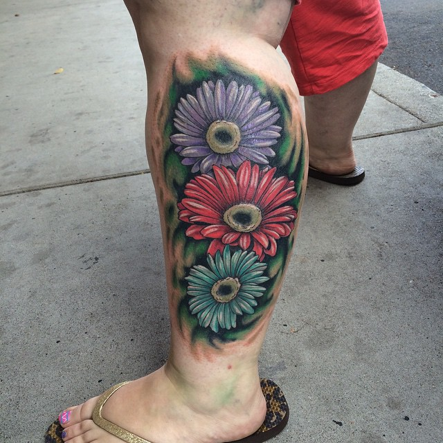 Colored Daisy Tattoos On Left Leg