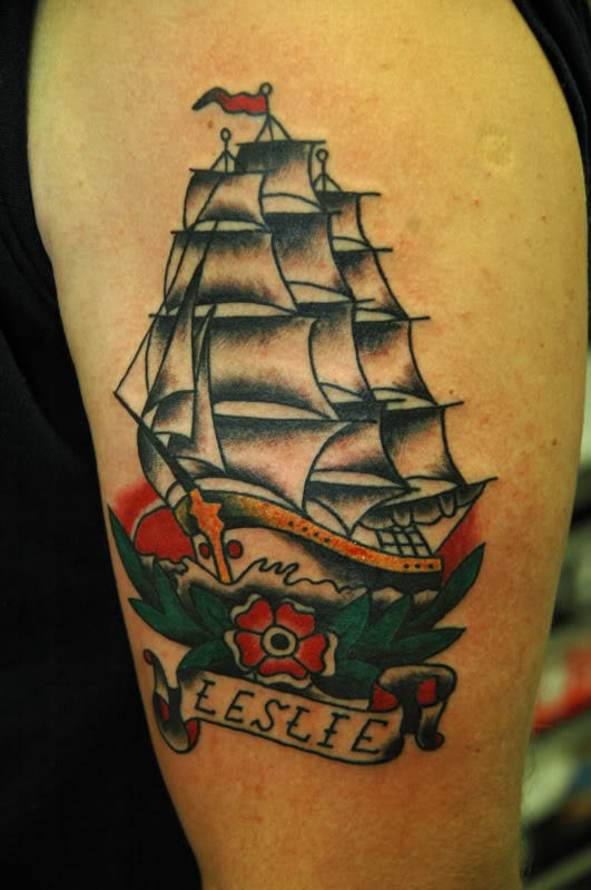 Traditional Flower And Ship Tattoo On Biceps