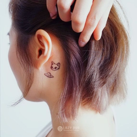 Tiny Cat Face And Alien UFO Tattoo Behind The Ear