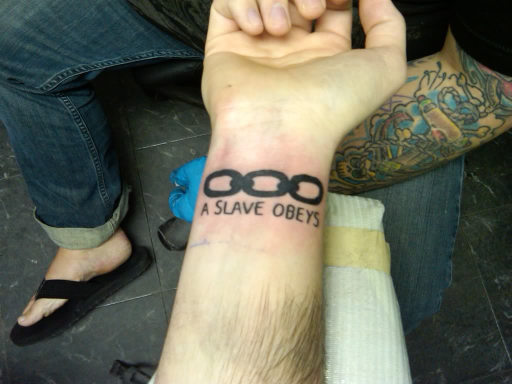 Black Chain With A Slave Obeys Tattoo On Wrist