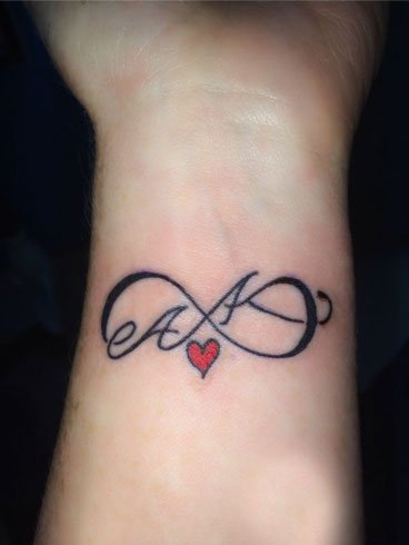 Black Ink Infinity Tattoo With Small Heart And Initials On Wrist